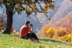 Mann, der Fotos unter Herbstbaum macht lizenzfreie stockfotografie