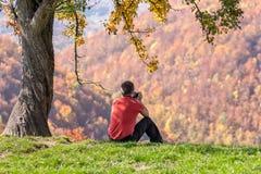 Mann, der Fotos unter Herbstbaum macht lizenzfreie stockbilder