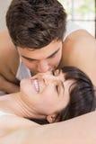 Mann, der Frau auf Bett küsst Lizenzfreie Stockbilder