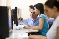 Mann, der Frau beim Computerraumlächeln unterstützt Lizenzfreie Stockbilder