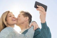 Mann, der Frau beim Nehmen des Selbstporträts am Handy küsst Lizenzfreies Stockfoto