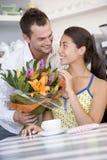Mann, der Frauenblumenstrauß der Blumen gibt Stockfotos