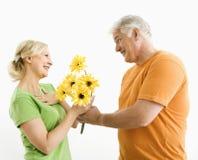 Mann, der Frauenblumenstrauß gibt. Stockbild