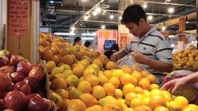 Mann, der frische Orange im Gemischtwarenladen vorwählt stock video