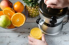 Mann, der frischen Orangensaft zubereitet Früchte im Hintergrund stockbilder