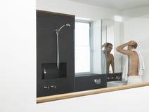Mann, der in Front Of Mirror sich überprüft Stockbilder