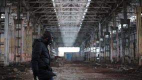Mann in der Gasmaske mit Schlüssel geht auf Hintergrund der verlassenen Fabrik stock video