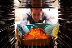 Mann, der gebackenen Brotlaib aus dem Ofen heraus nimmt Lizenzfreies Stockbild