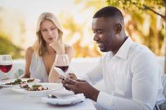 Mann, der gebohrte Frau bei der Anwendung des Handys ignoriert Stockbild
