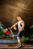 Mann, der Gebrüll eine Brücke mit Kesselglocke ausarbeitet lizenzfreies stockfoto
