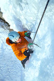 Mann, der gefrorenen Wasserfall klettert Lizenzfreie Stockfotos