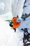 Mann, der gefrorenen Wasserfall klettert Stockbild