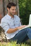 Mann, der gegen einen Baum sitzt Stockbild