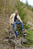 Mann, der gegen einen Baumstumpf stützt Stockfoto