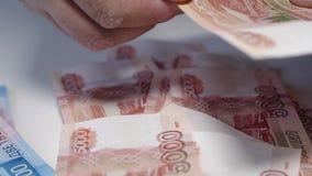 Mann, der Geld, Banknoten des russischen Rubels, über seiner Bestechung des Schreibtisches I und Korruptionskonzept gibt Russisch stock video