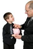 Mann, der Geld in Jungen-Piggy Querneigung einsetzt Lizenzfreie Stockbilder