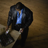 Mann, der Geld am Schreibtisch zählt Lizenzfreies Stockfoto