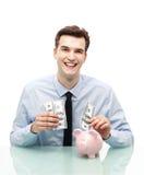 Mann, der Geld in Sparschwein einsetzt Lizenzfreie Stockfotos