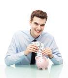 Mann, der Geld in Sparschwein einsetzt Lizenzfreies Stockfoto