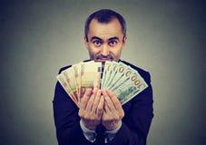 Mann, der Geldeuro und Dollar Banknoten hält Lizenzfreie Stockfotos