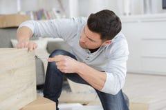 Mann, der gelieferte Möbel zusammenbaut Stockfoto
