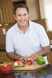 Mann, der Gemüse hackt Stockfotos