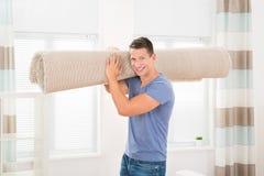 Mann, der gerollten Teppich trägt stockfotografie