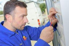 Mann, der geschädigtes fusebox kontrolliert stockfotos