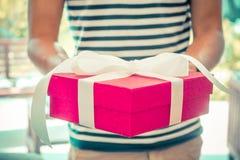 Mann, der Geschenk in einem rosa Kasten gibt stockbild