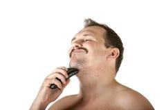 Mann, der Gesicht mit Elektrorasierer rasiert Stockfoto