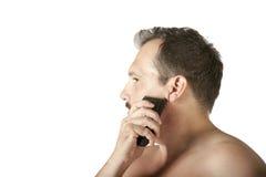 Mann, der Gesicht mit Elektrorasierer rasiert Lizenzfreie Stockfotografie