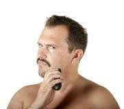 Mann, der Gesicht mit Elektrorasierer rasiert Stockbilder