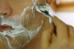 Mann, der Gesicht mit Rasiermesser rasiert stockfoto