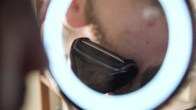 Mann, der Gesicht mit Trimmer im Spiegel-Abschluss oben rasiert stock footage