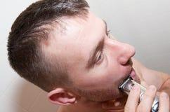 Mann, der Gesicht rasiert Stockfotografie