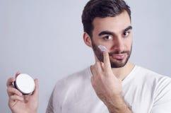 Mann, der Gesichtscreme auf Backen aufträgt lizenzfreie stockfotos
