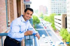 Mann, der Getränk auf äußerem Balkon genießt lizenzfreies stockbild