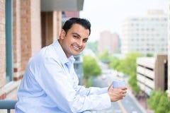 Mann, der Getränk auf äußerem Balkon genießt stockfotos