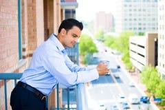 Mann, der Getränk auf äußerem Balkon genießt stockbilder