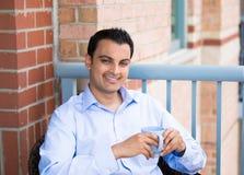 Mann, der Getränk auf äußerem Balkon genießt stockfoto