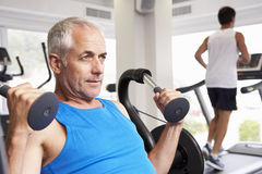 Mann, der Gewichts-Maschine mit Läufer auf Tretmühle im Hintergrund verwendet Stockfoto