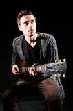 Mann, der Gitarre in der Dunkelkammer spielt Lizenzfreies Stockfoto