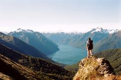 Mann, der Glazial- See und Berge ansieht
