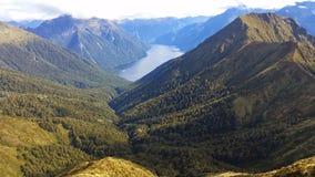 Mann, der Glazial- See und Berge ansieht Stockfotos