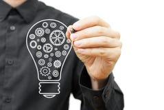 Mann, der Glühlampe mit Kettenrädern zeichnet Vision, Idee und innovati Lizenzfreie Stockfotos
