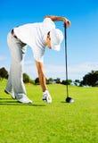 Mann, der Golfball auf T-Stück platziert Lizenzfreie Stockfotos