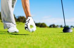 Mann, der Golfball auf T-Stück platziert Stockfotos