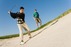 Mann, der Golfball aus einem Sandfang heraus abbricht Stockfotos