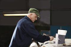 Mann in der grünen Kappe, die an Maschine arbeitet Stockfotografie