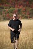 Mann, der in Gras läuft Stockfotos